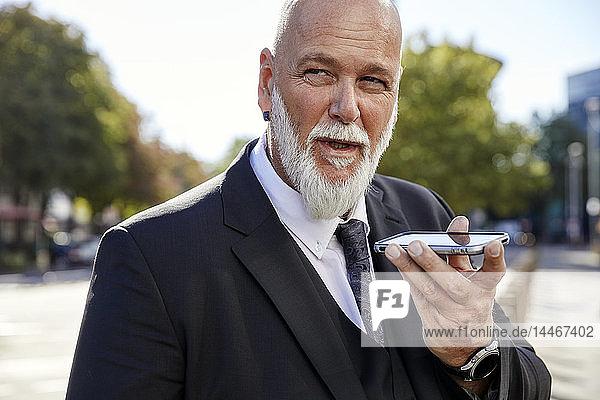 Elegant businessman using smartphone in the city