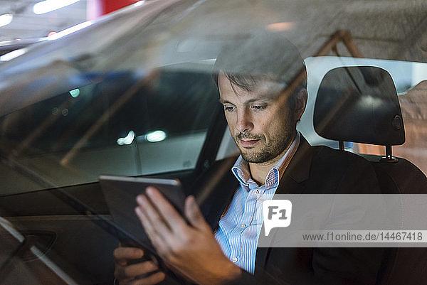 Geschäftsmann  der nachts im Auto sitzt und ein digitales Tablet benutzt