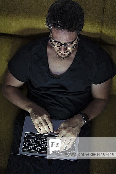 Man sitting on couch using laptop at night