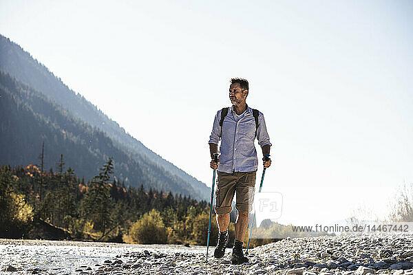 Österreich  Alpen  Mann auf einer Wanderung auf Kieselsteinen entlang eines Baches