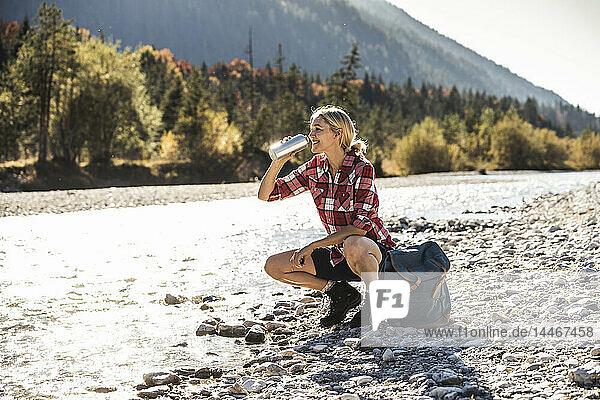 Österreich,  Alpen,  Frau auf Wanderung mit Rast an einem Bach