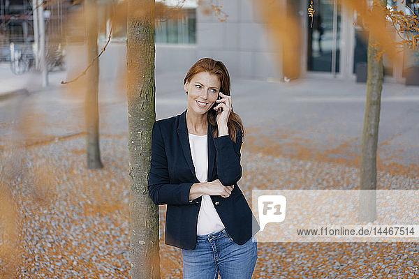 Lächelnde Geschäftsfrau am Handy im Herbst draußen in der Stadt