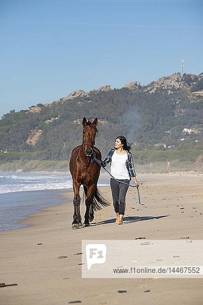 Spanien  Tarifa  Frau mit Pferd am Strand spazieren