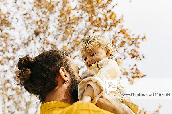Vater hält seine Tochter morgens im Herbst in einem Park