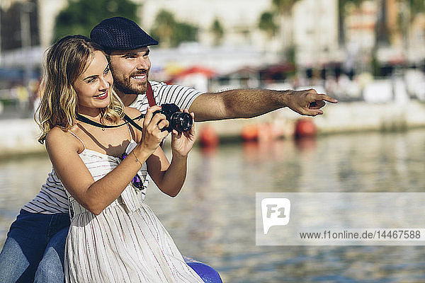 Spain  Andalusia  Malaga  happy tourist couple taking photographs at the harbor