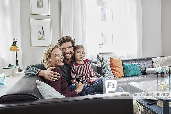 Portrait of happy family sitting on couch at home