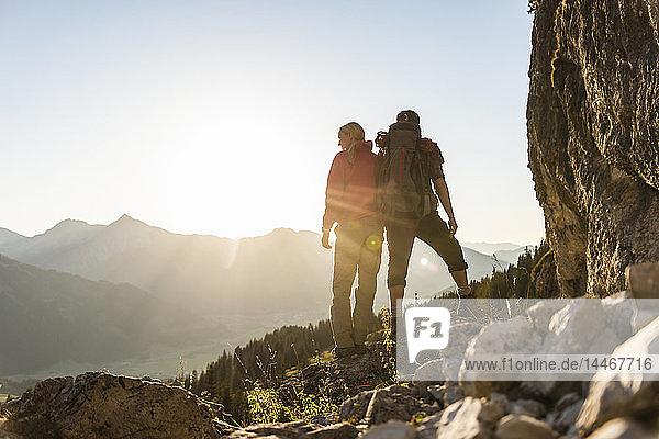 Paar steht auf einem Berg und schaut auf die Aussicht