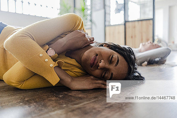 Smiling young woman lying on wooden floor with closed eyes
