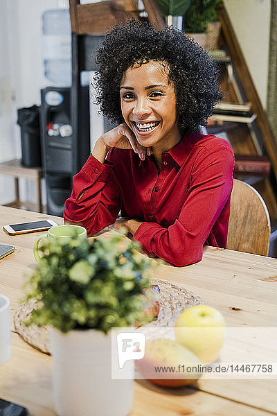 Portrait of happy woman sitting at table