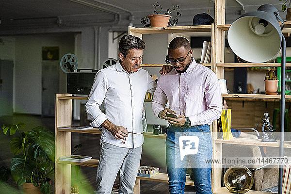 Zwei Geschäftsleute telefonieren in einem Loft-Büro