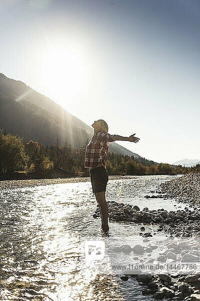 Österreich,  Alpen,  Frau auf einer Wanderung im Bach stehend