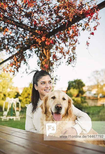 Smiling young woman with her Golden retriever dog resting in a park