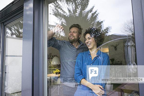 Glückliches Paar zu Hause hinter dem Fenster und schaut hinaus