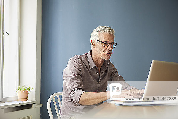 Mature man using laptop on table at home