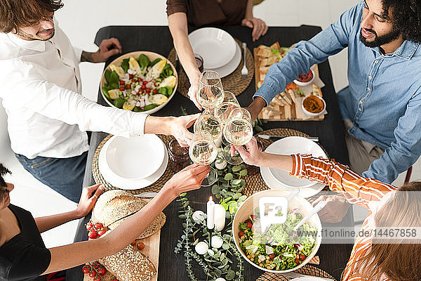 Friends having a dinner party  clinking glasses  view from above