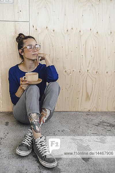 Junge Frau macht eine Pause im Büro und trinkt Kaffee aus einer Holztasse