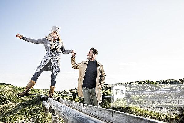 Mann hilft Frau beim Balancieren auf Holzpfählen in den Dünen