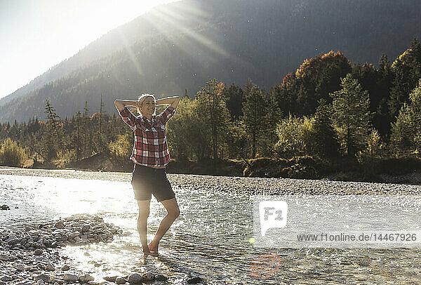 Österreich  Alpen  Frau auf Wanderung  die in einem Bach watend