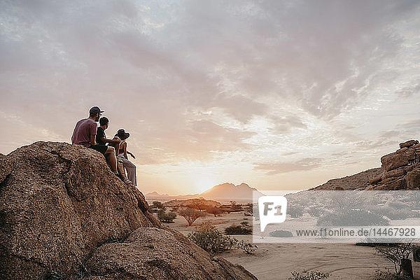 Namibia  Spitzkoppe  Freunde sitzen auf einem Felsen und beobachten den Sonnenuntergang