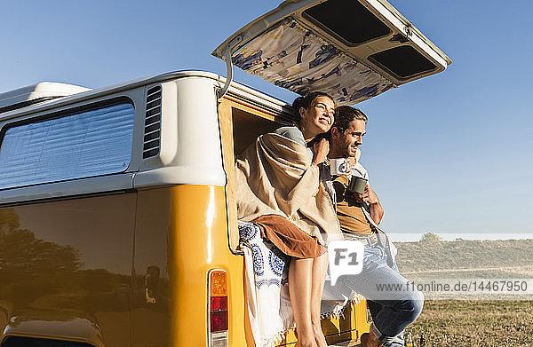 Ein glückliches Paar  das mit seinem Wohnmobil eine Reise macht  auf dem Bett sitzt und Kaffee trinkt