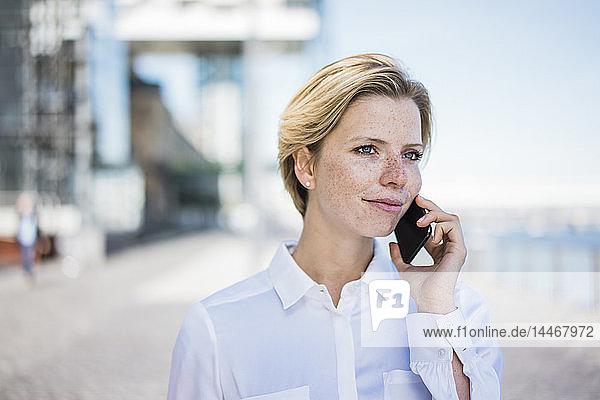 Junge Geschäftsfrau benutzt Mobiltelefon