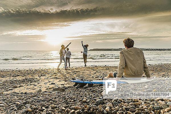 Junger Mann auf dem Surfbrett beobachtet Freunde beim Seifenblasenmachen am Strand bei Sonnenuntergang