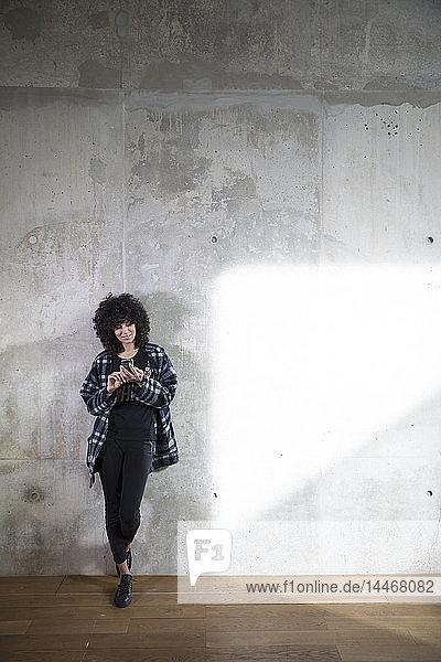 Frau lehnt mit Handy an Betonwand