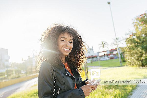 Porträt einer lächelnden jungen Frau mit Smartphone im Freien