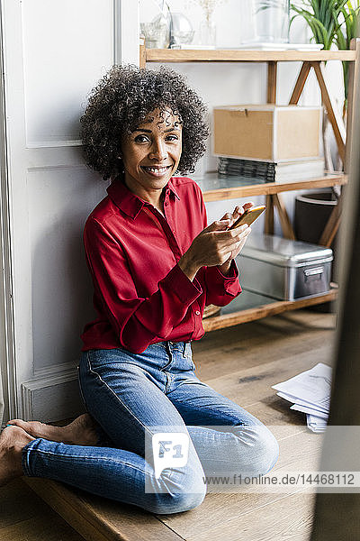 Portrait of smiling woman sitting on the floor at home with cell phone