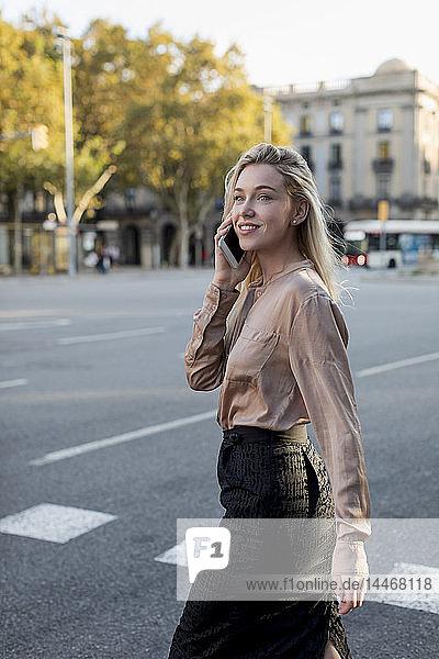 Lächelnde junge Geschäftsfrau am Handy in der Stadt unterwegs