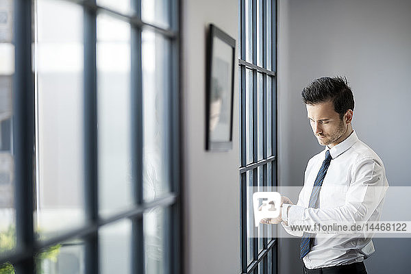 Businessman checking smartwatch in front of large office window