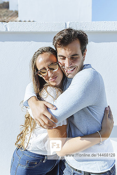 Lächelndes Paar umarmt sich an einem sonnigen Tag