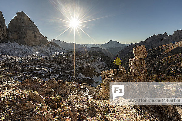 Italy  Tre Cime di Lavaredo  man hiking and looking at the valley with peaks and sun over the horizon