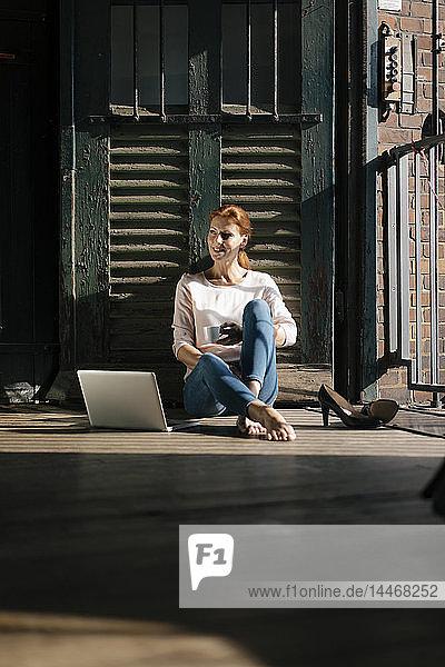 Lächelnde Geschäftsfrau sitzt auf dem Boden mit Tasse Kaffee und Laptop