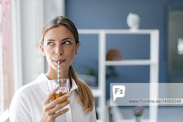 Junge Frau trinkt Tee mit einem Strohhalm