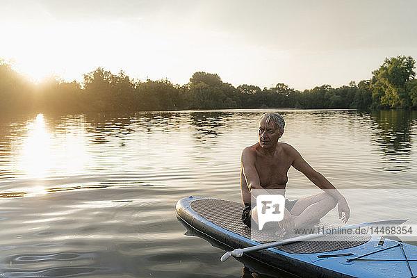 Älterer Mann sitzt bei Sonnenuntergang im SUP-Vorstand
