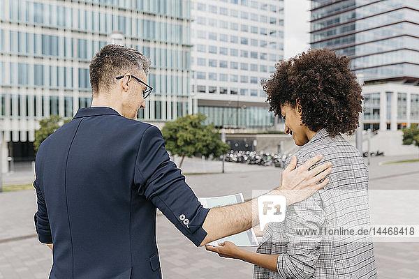 Zwei Kollegen betrachten Papier vor dem Bürogebäude