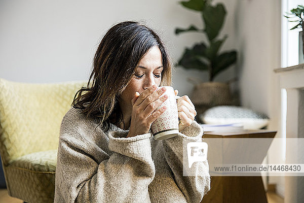 Woman sitting in her comfortable home  drinking tea