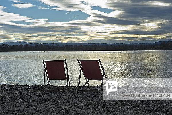 Deutschland  zwei leere Liegestühle stehen bei Sonnenuntergang am Ufer des Ammersees