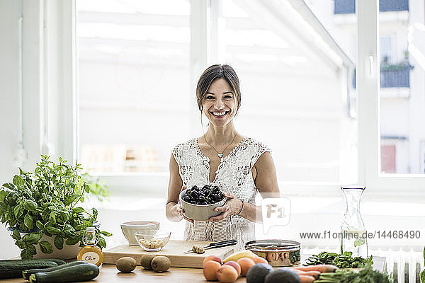 Woman preparing healthy food in her kitchen  holding bowl of cherries