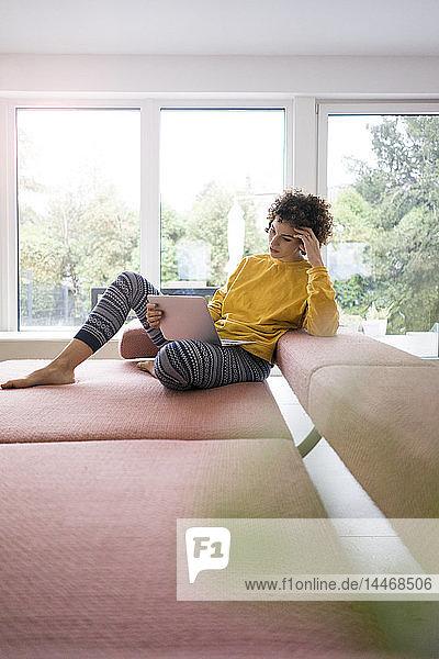 Frau benutzt Laptop auf der Couch zu Hause