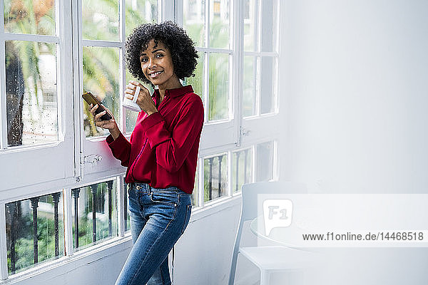 Portrait of smiling woman with cup of coffee and cell phone standing at the window at home