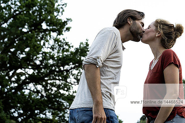 Happy couple in nature  standing face to face  kissing each other