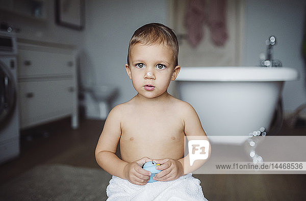 Portrait of toddler boy holding a toy duck in a bathroom at home