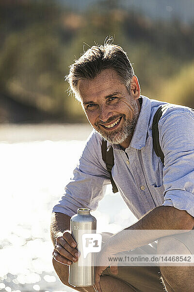 Österreich  Alpen  Porträt eines lächelnden Mannes auf einer Wanderung mit einer Abkühlungspause
