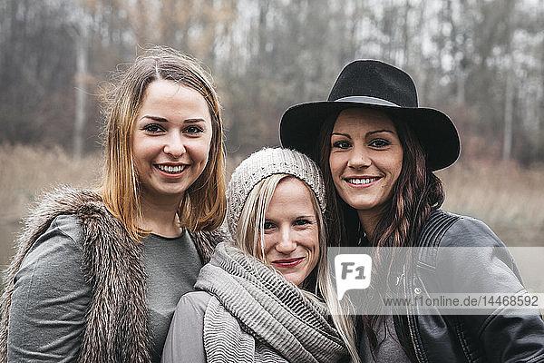 Porträt von drei glücklichen Freunden im Herbst