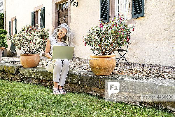 Frau mit langen grauen Haaren sitzt mit Laptop auf der Terrasse eines Landhauses