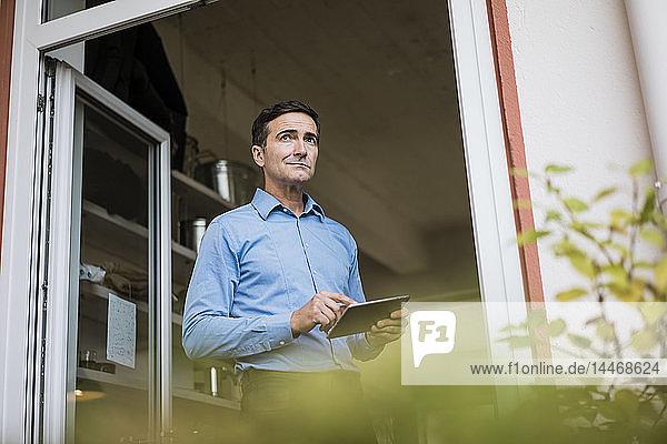 Geschäftsmann mit Tablette vor offener französischer Tür