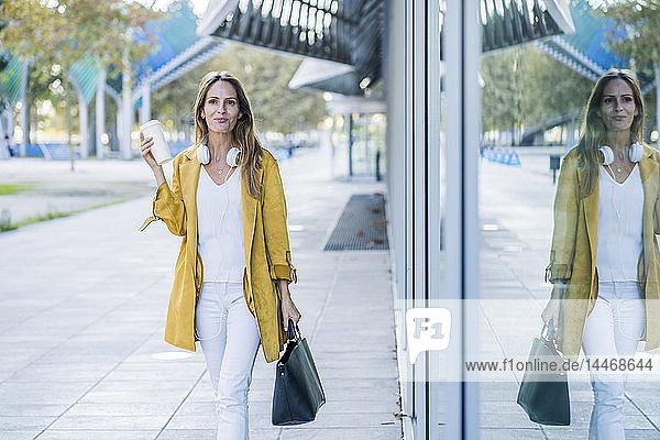 Woman with handbag and takeaway coffee walking along building