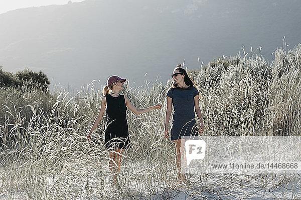 Südafrika  Western Cape  Hout Bay  zwei junge Frauen  die in den Dünen spazieren gehen und dabei sprechen